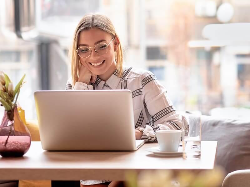 Blonde Frau am Laptop im Café
